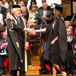 chancellor shaking a student's hand on stage at graduation