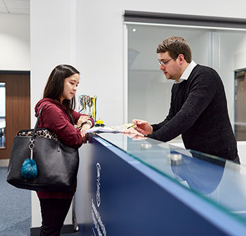 Student talking to a member of the Academic Experience and Support Team at The College's reception desk.
