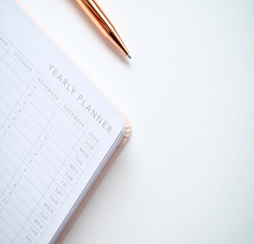Close up image of a yearly planner with a gold pen beside it