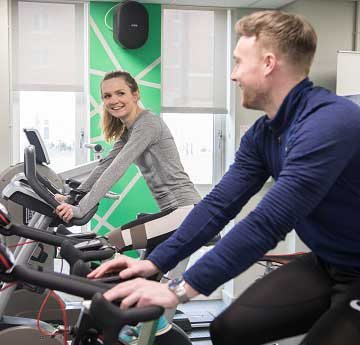 A male and female on cycling machines in Bay gymnasium.
