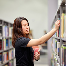 Female student looking for books in a library