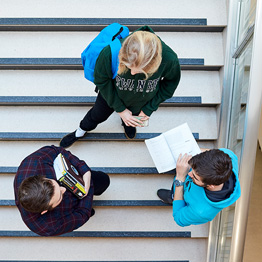 Aerial photo of three students on a staircase talking