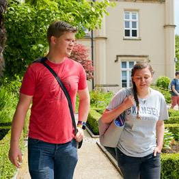 Male and female student walking next to Singleton Abbey