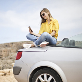 Girl in yellow t-shirt sitting on the back of a convertible car looking at her mobile phone