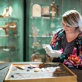 Museum curator handling Egyptian artefacts