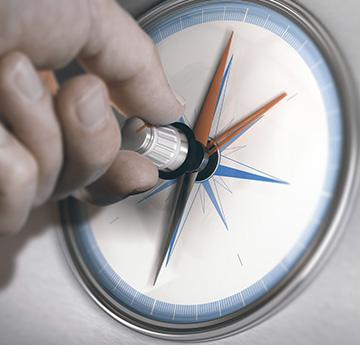 hand turning the point on a compass