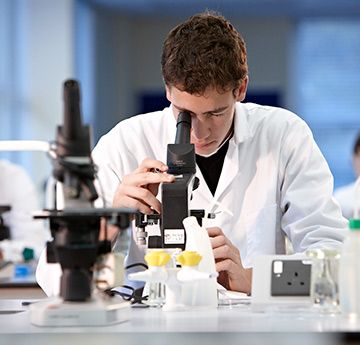 A male staff member looking into a microscope.