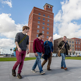 Group of male students walking in front of the Tower Information Centre on Swansea University's Bay Campus
