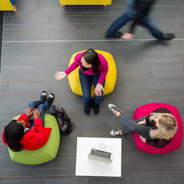 Aerial photo of three students sitting on colourful beanbags chatting