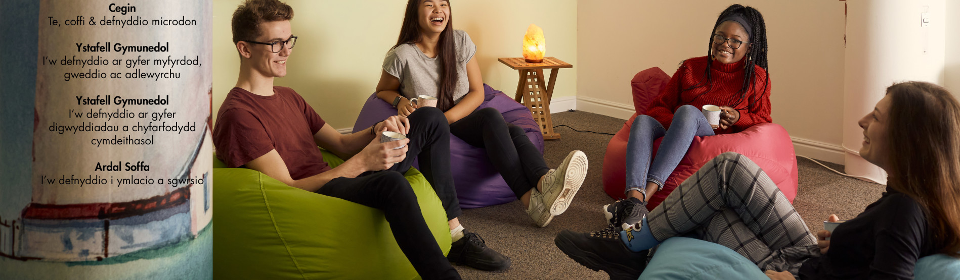 Four students are sitting on beanbags in The Lighthouse, Singleton Campus. They are holding mugs and smiling.
