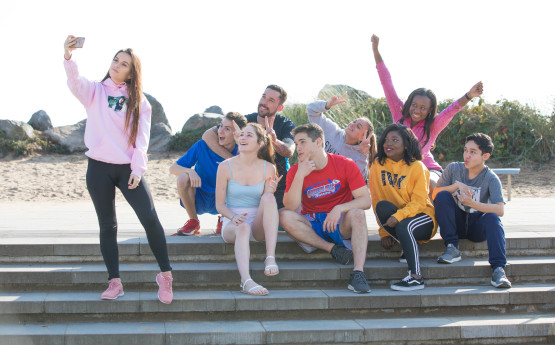 Image shows a group of students, posing for a selfie sitting on some concrete steps.