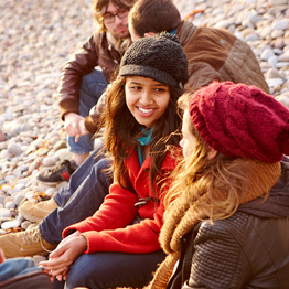 Group of students sitting on a pebble beach