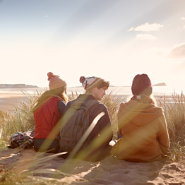 Three students sitting on the sand dunes of a beach talking and looking out to sea